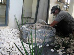 אלמנט מים מבזלת קדוחה אשר בתוכה סלע נוסף מבעבע שתילת צמחים וחיפוי חלוקי נחל לבנים