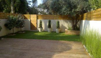 עיצוב גינה חסכונית במים בניית דק אורן גדר עץ ואדניות מעץ גושני